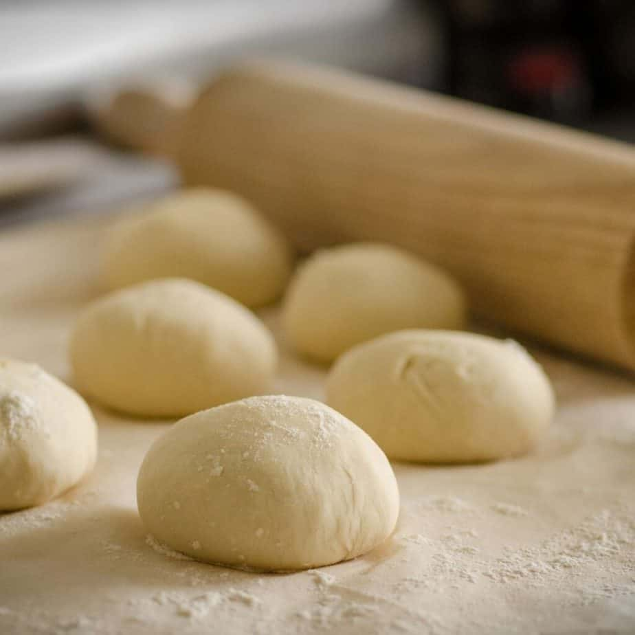 balls of uncooked dough on a surface with a rolling pin in the background