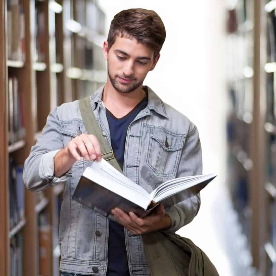 a man standing in a library flipping through a book