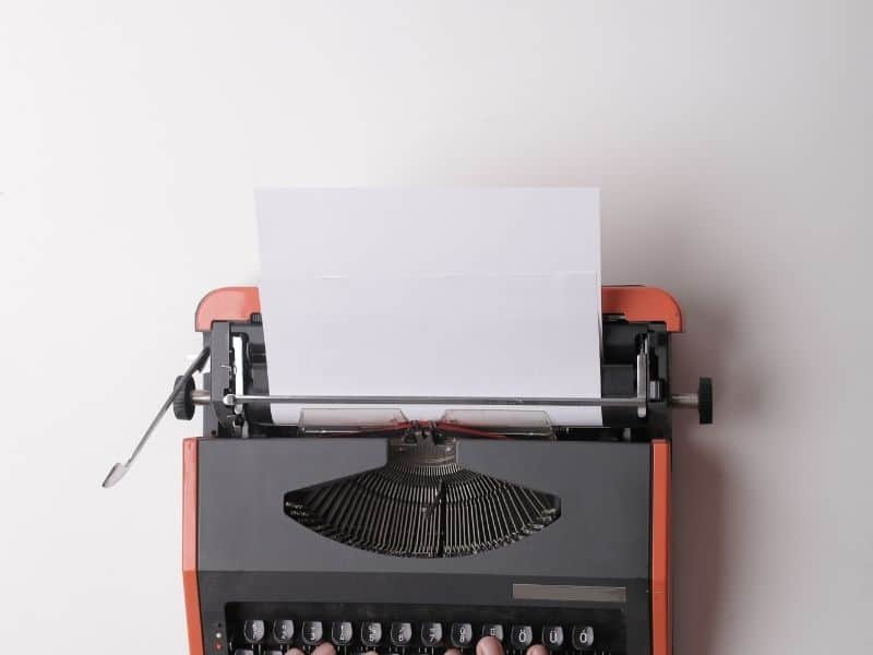 a red and black typewriter on a white table