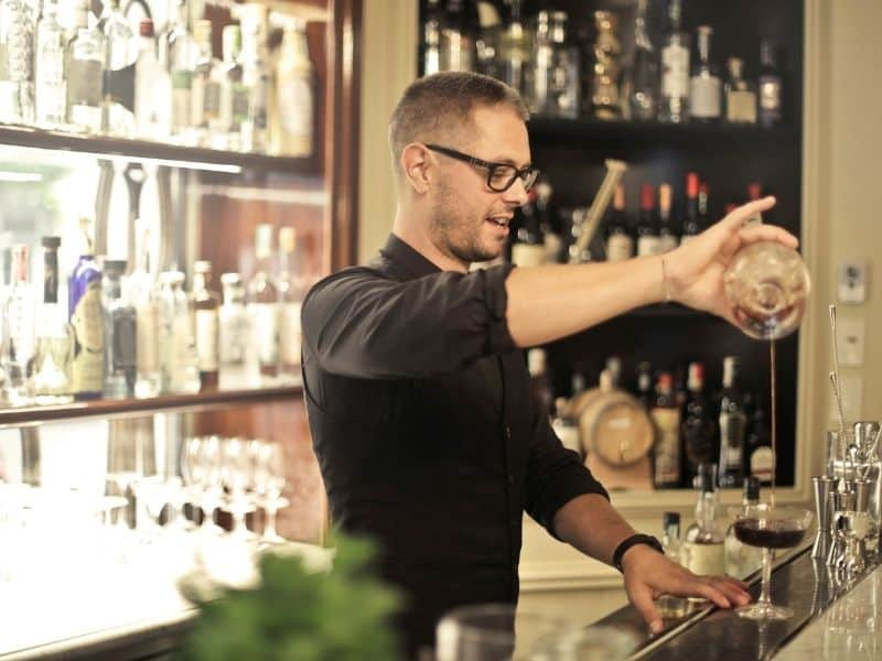 a bartender mixing a drink at the bar