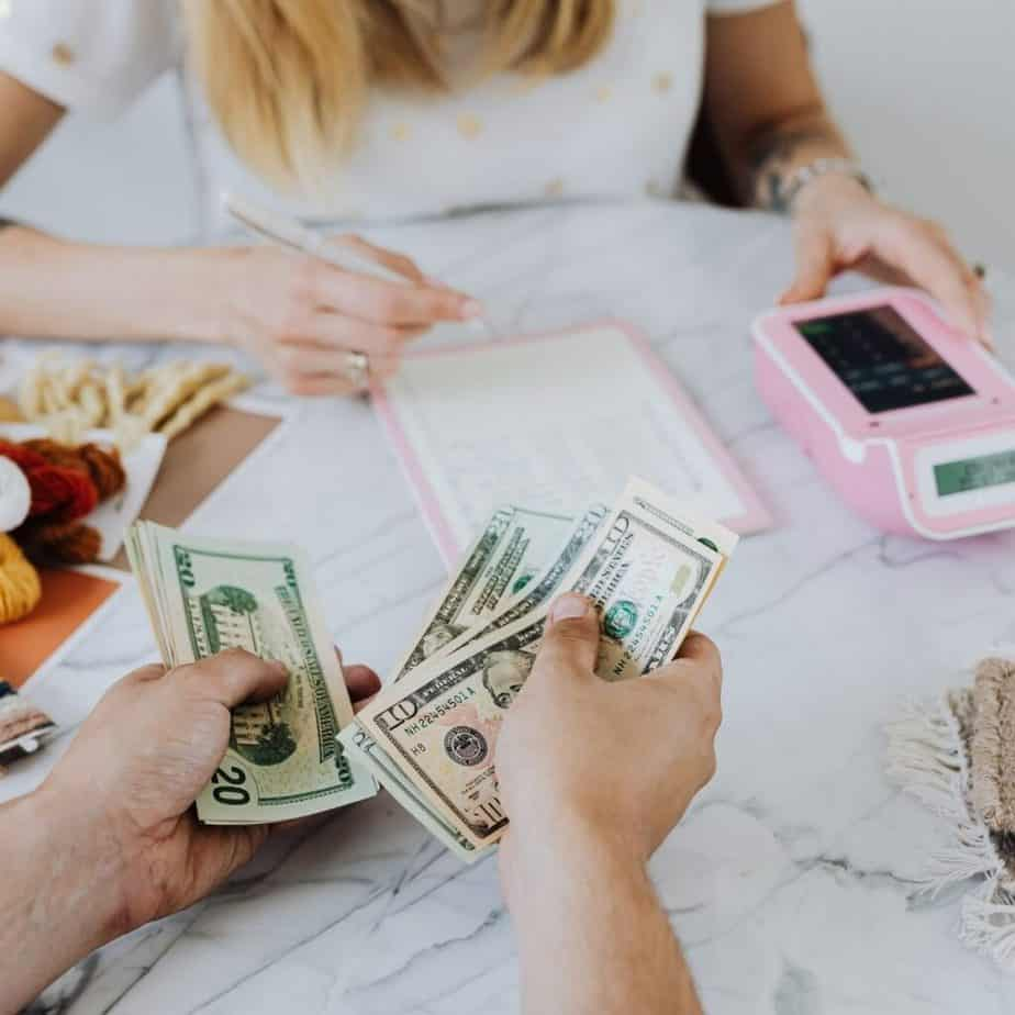 hands counting dollars over a table with notebook and calculators