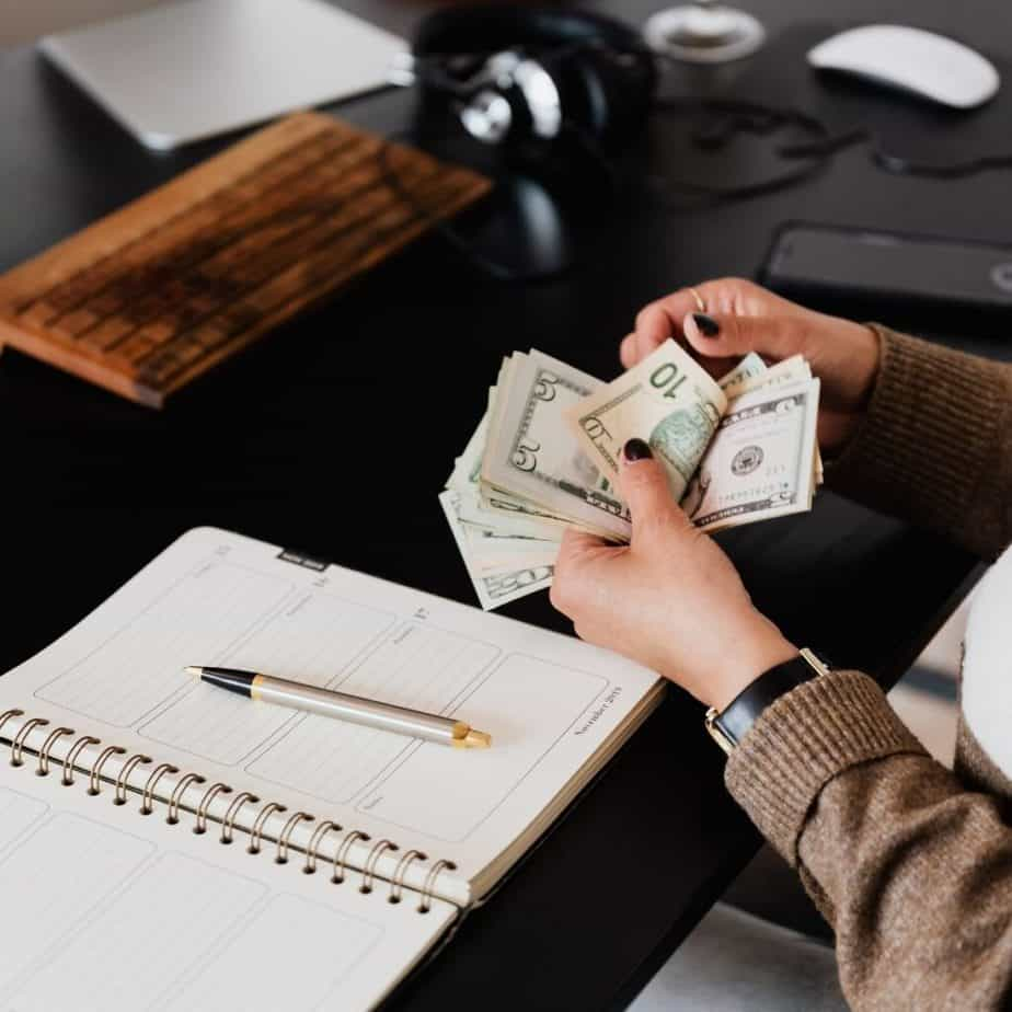 a womans hands coutning money over top a desk