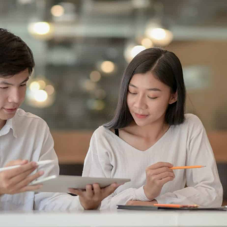 a couple sitting at a table together looking at a tablet