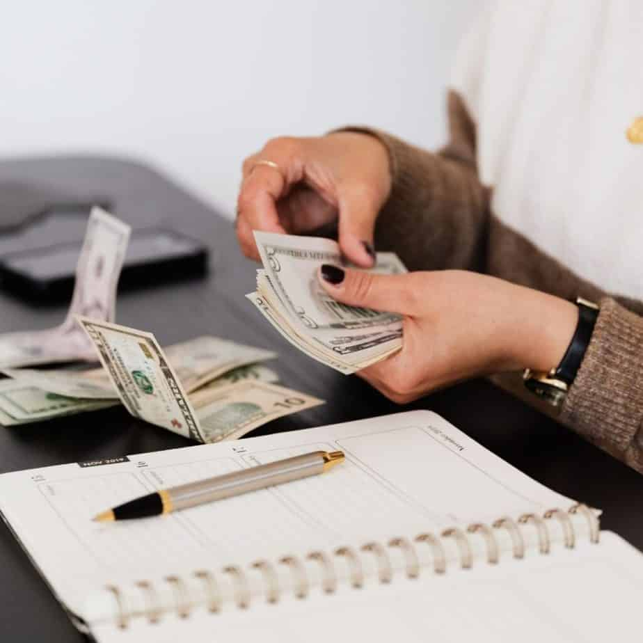 a woman couting money over a desk with a notebook on the side