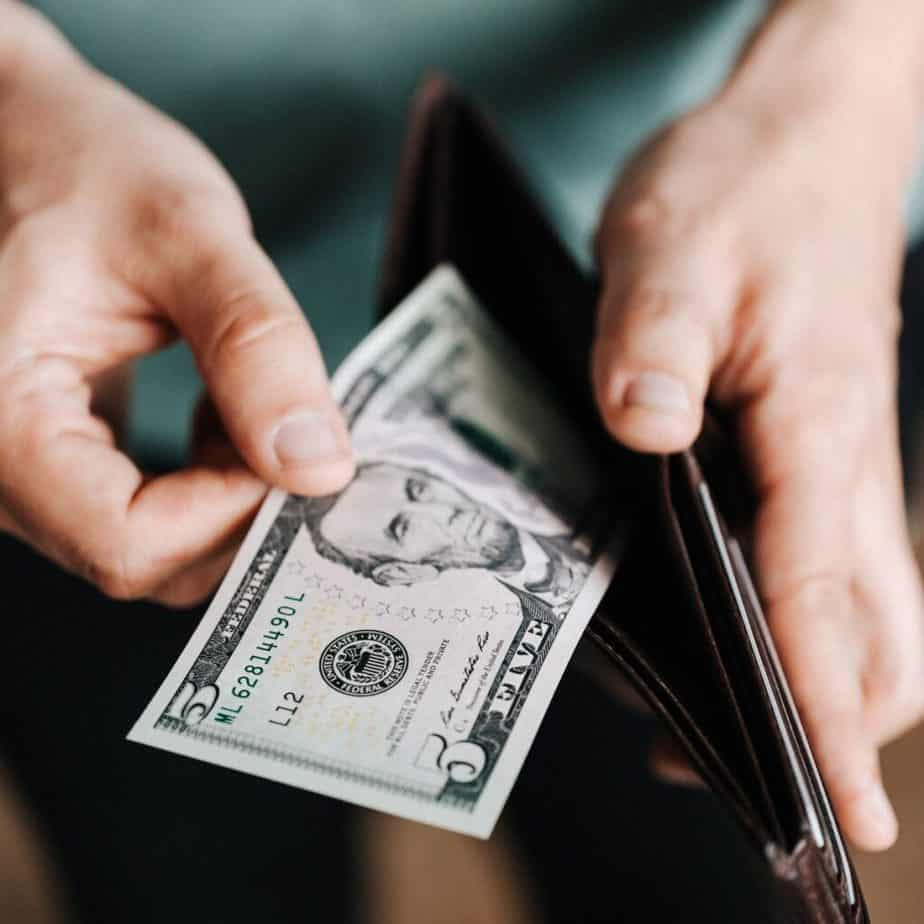 hands putting money into a wallet