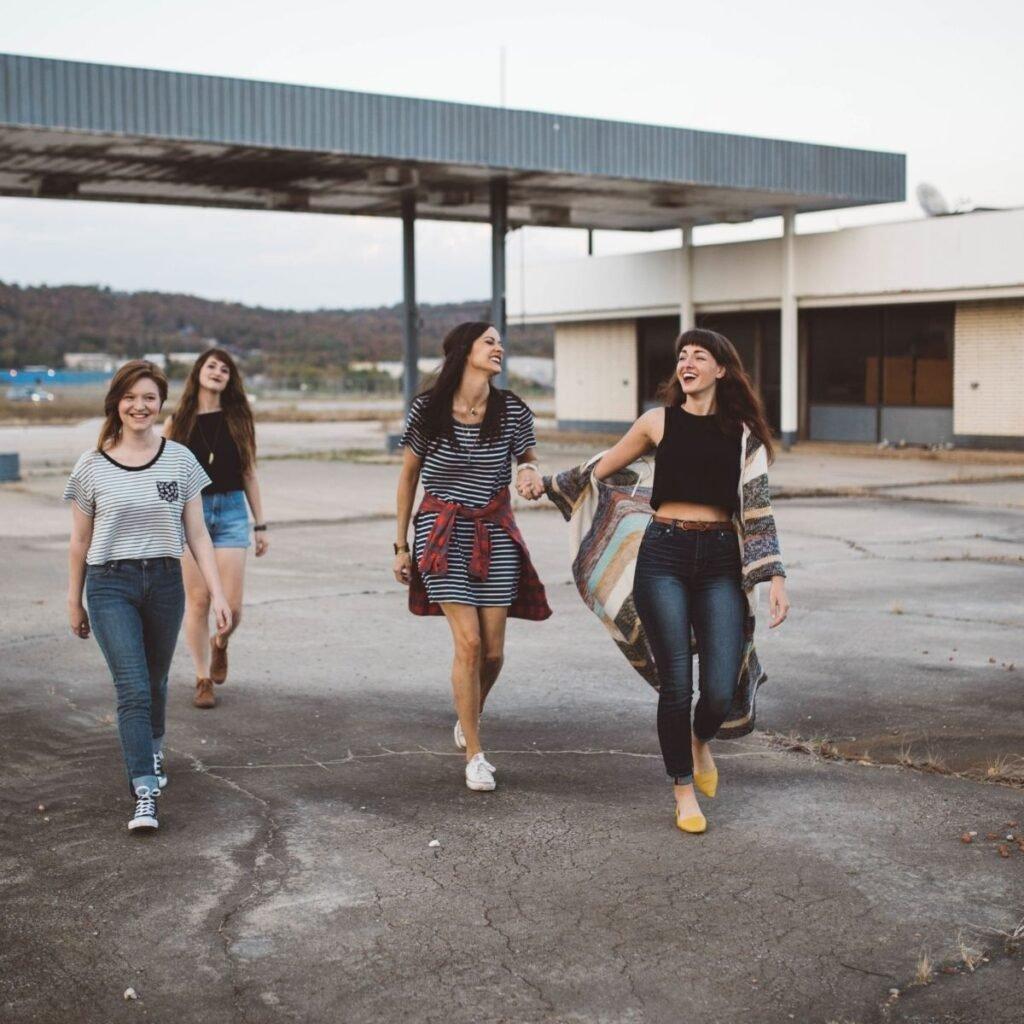 4 girls walking across an abandoned gas station lot