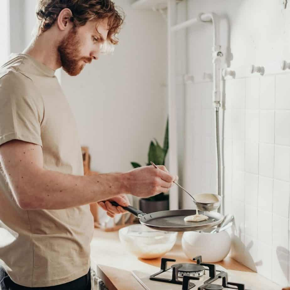 a man pouring sauce on a plate in a kitchen