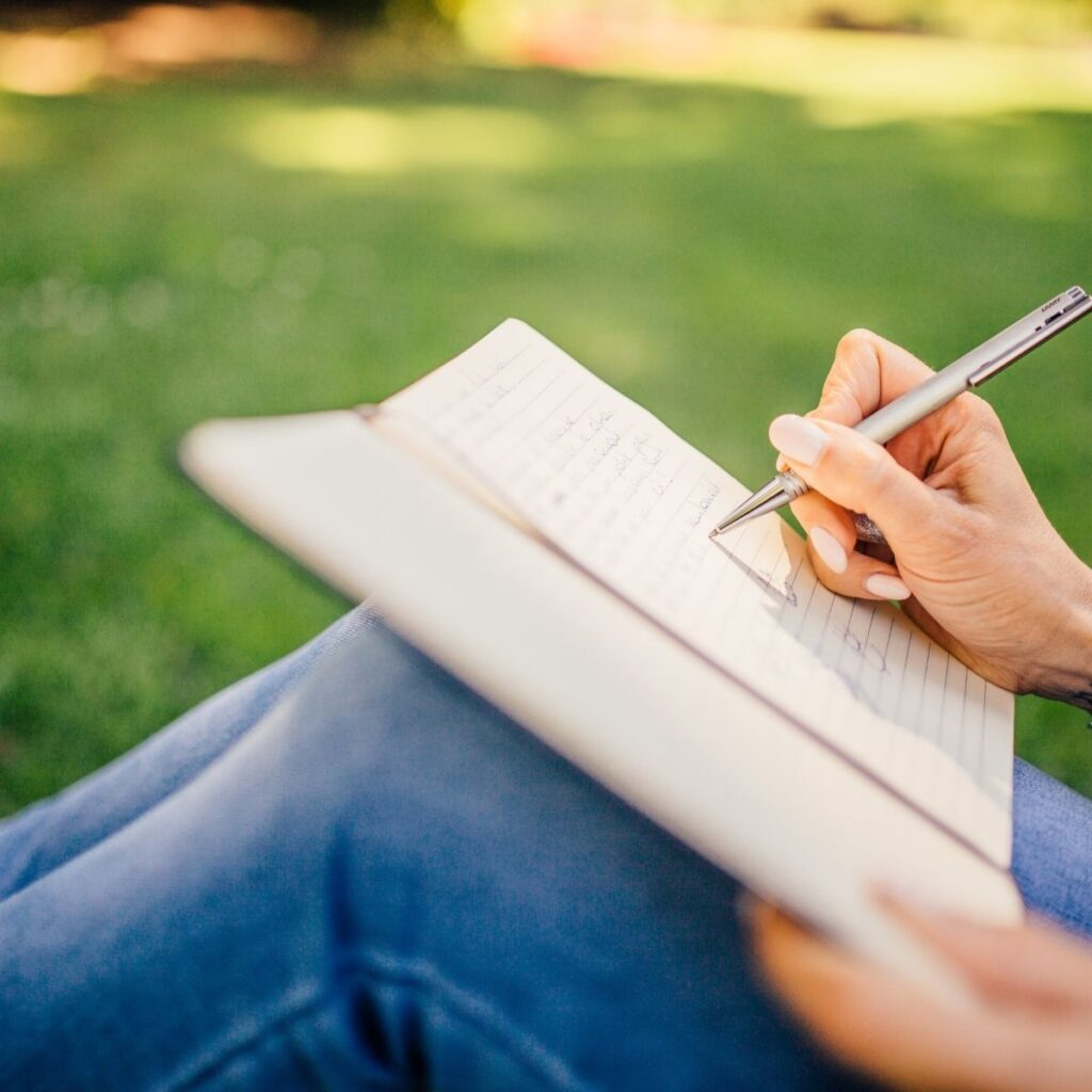 a person writing in a notebook outside
