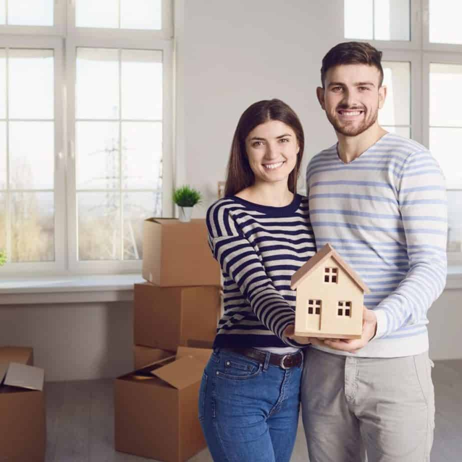a couple holding a small model house smiling at the camera