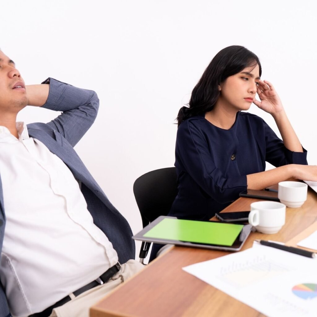 two people sitting at a conference table looking bored