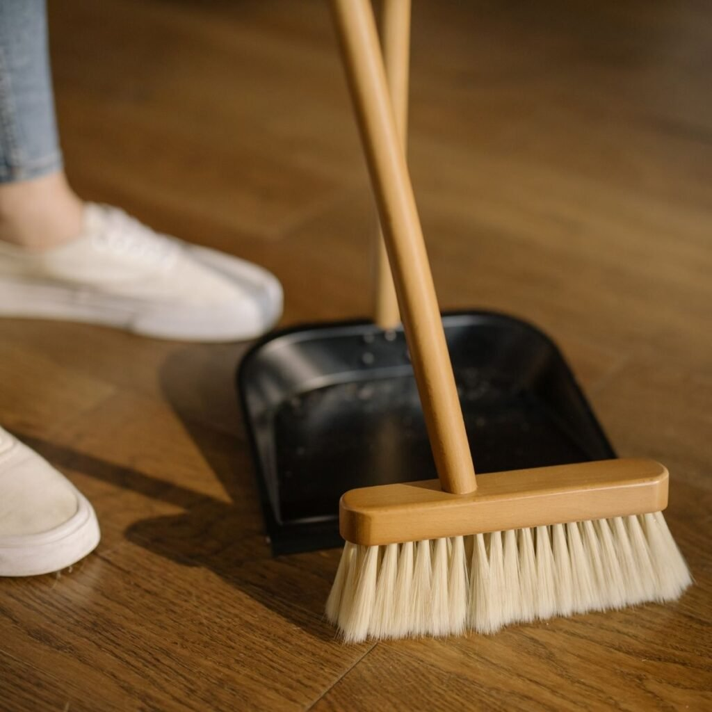 a woman sweeping with a broom and dustpan