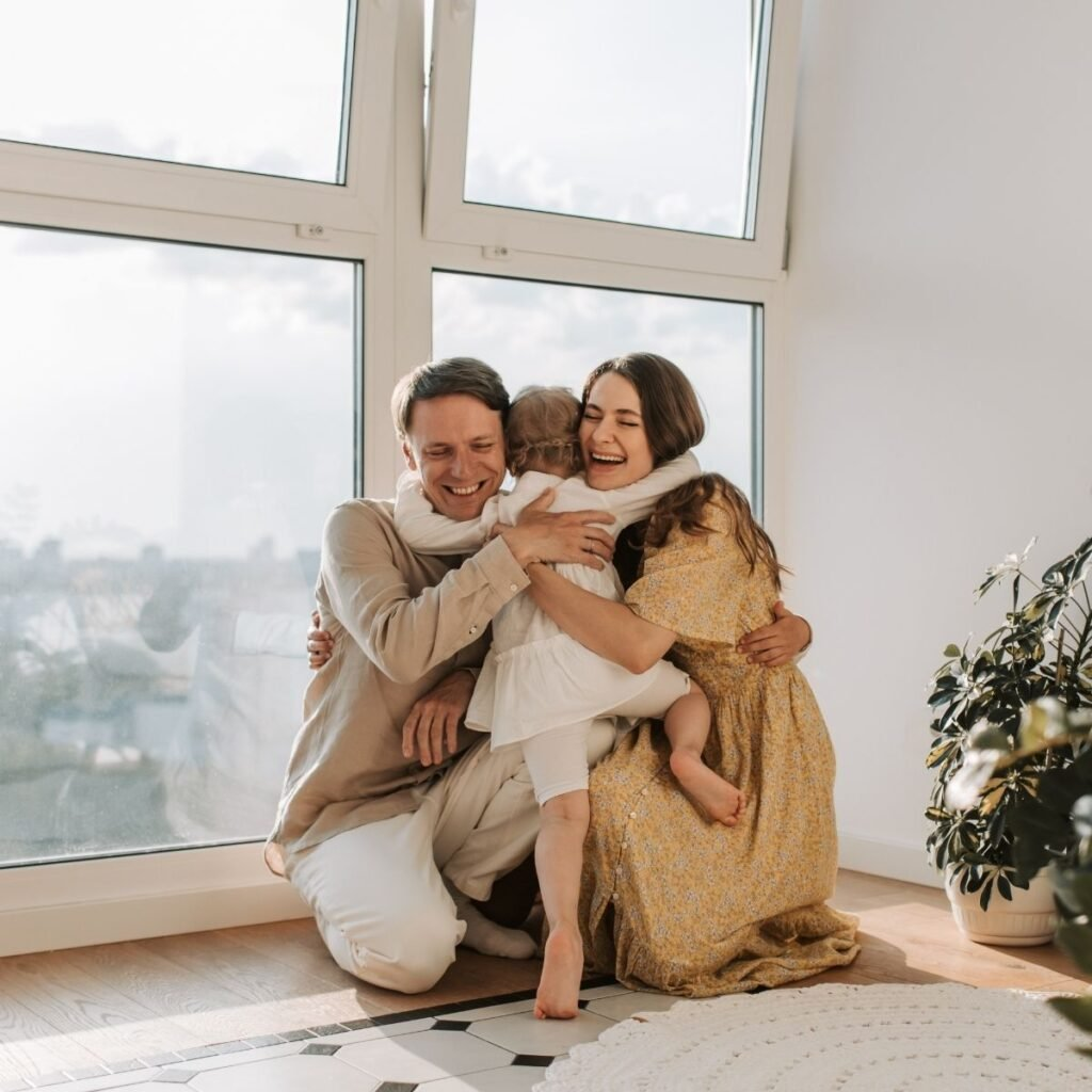 a family hugging in front of windows