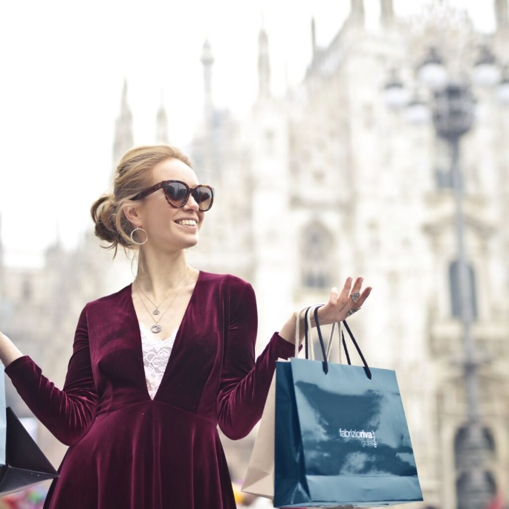 a woman holding shopping bags wearing sunglasses