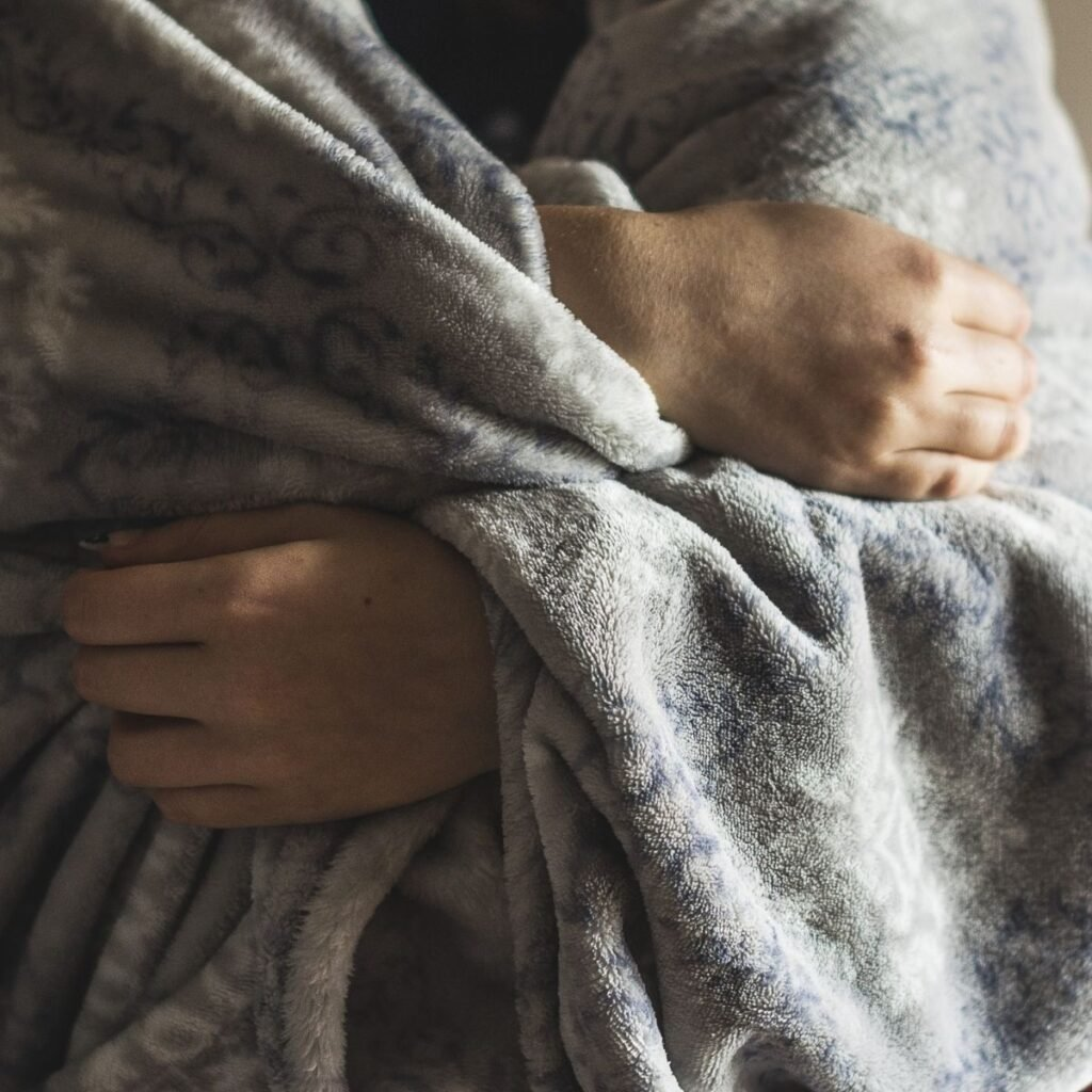 a person wrapped in a blanket holding it closed
