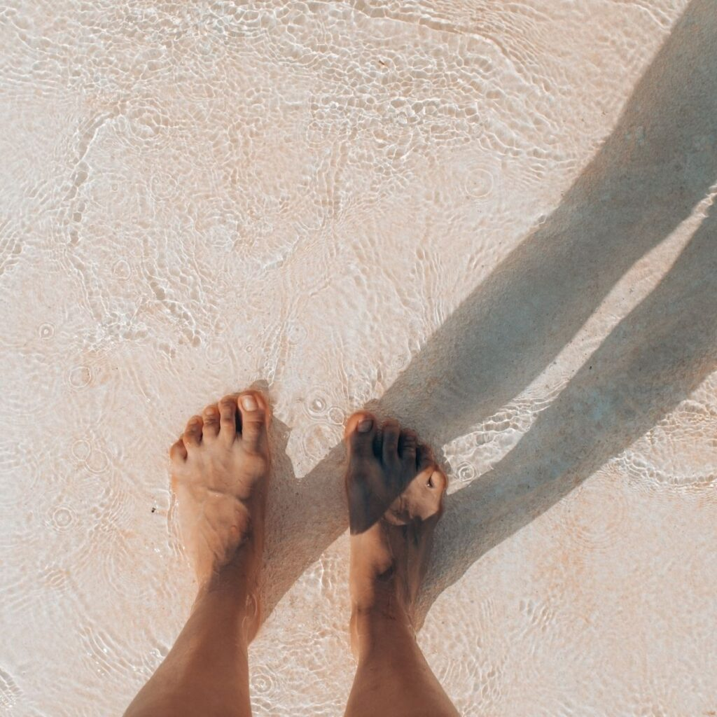 feet standing on sand and water