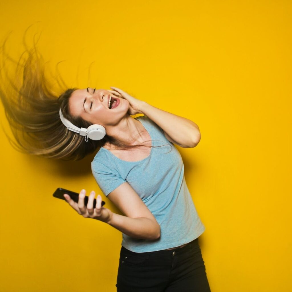 a woman dancing with headphones on in front of a yellow background