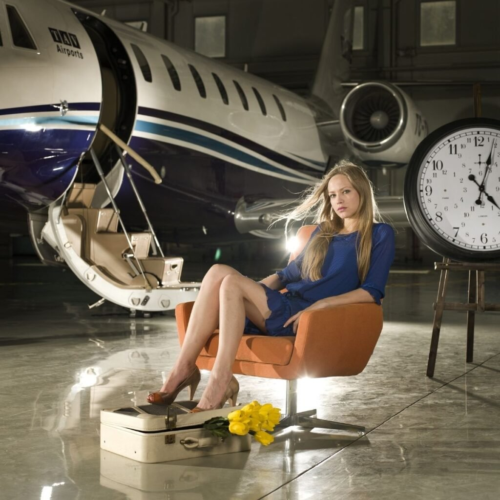 a woman sitting in a chair in front of a private jet