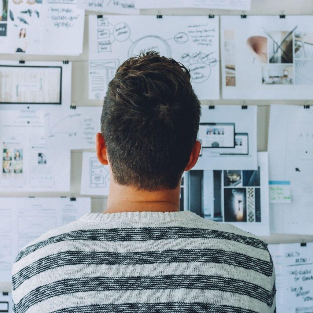 a man looking at a wall of diagrams