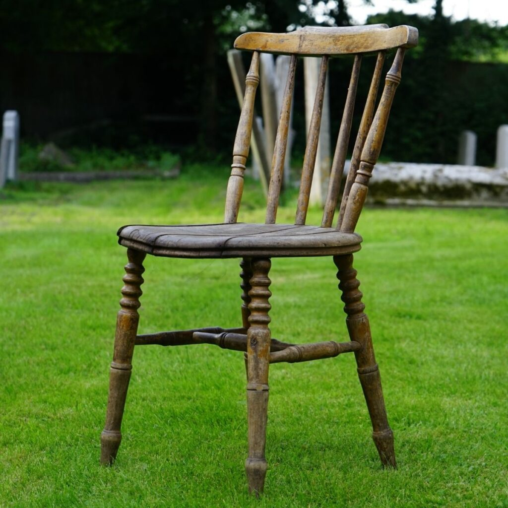 a wooden chair sitting on grass outside