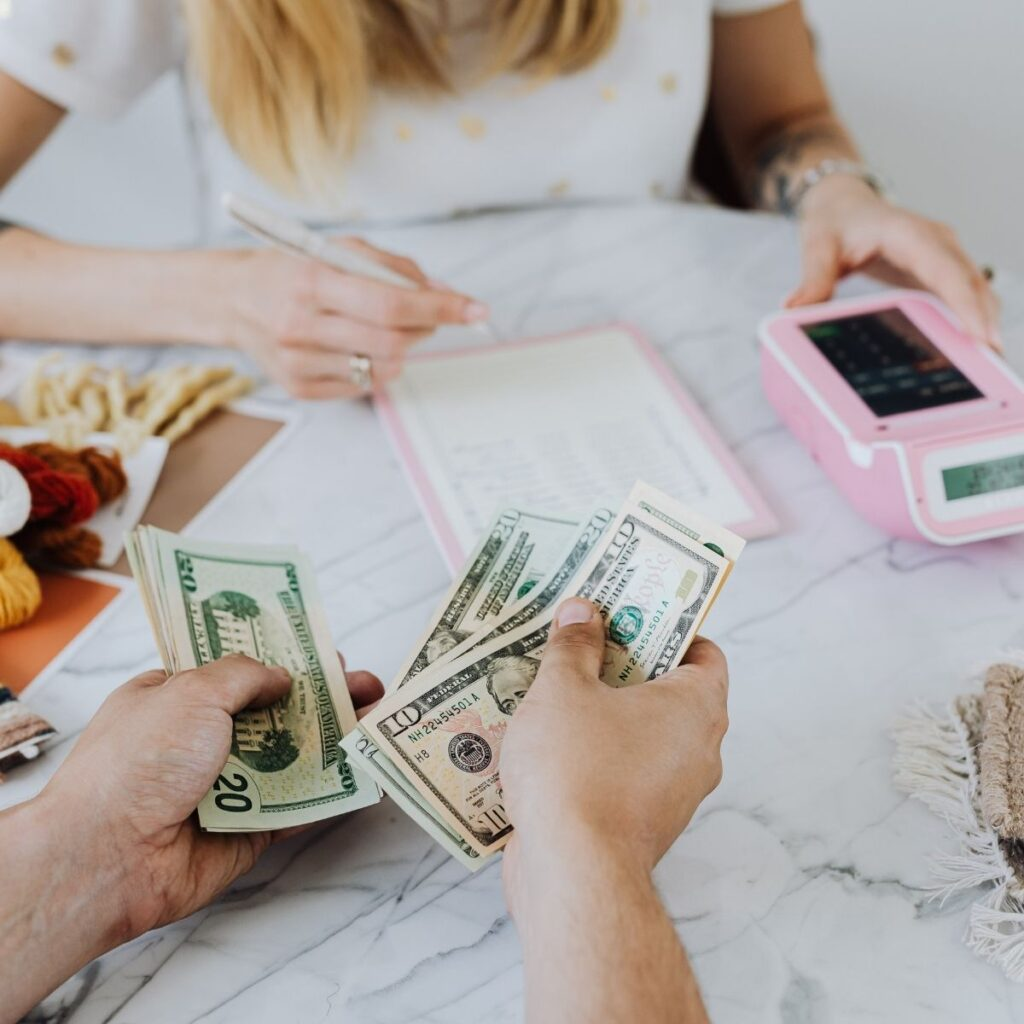 hands counting money on a table with a woman with a calculator in the background