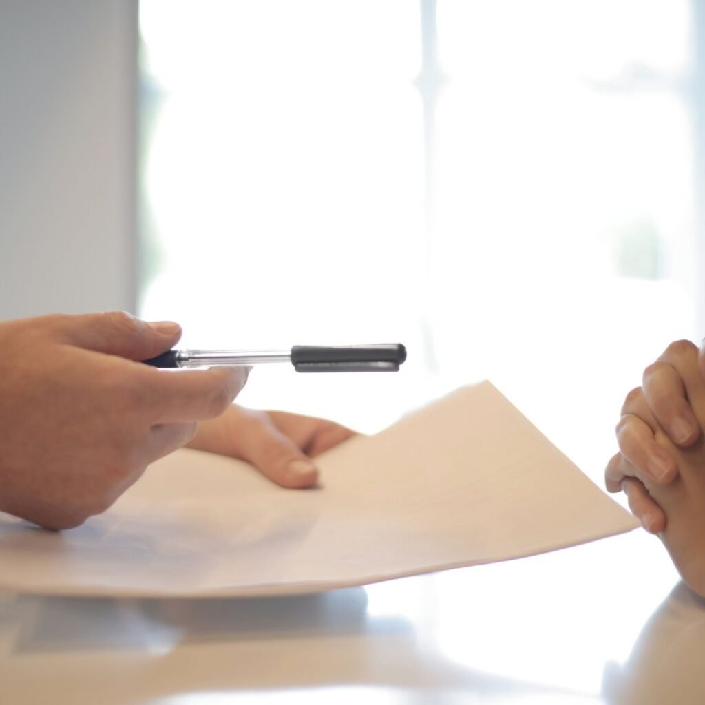 hands handing a document and pen to another person
