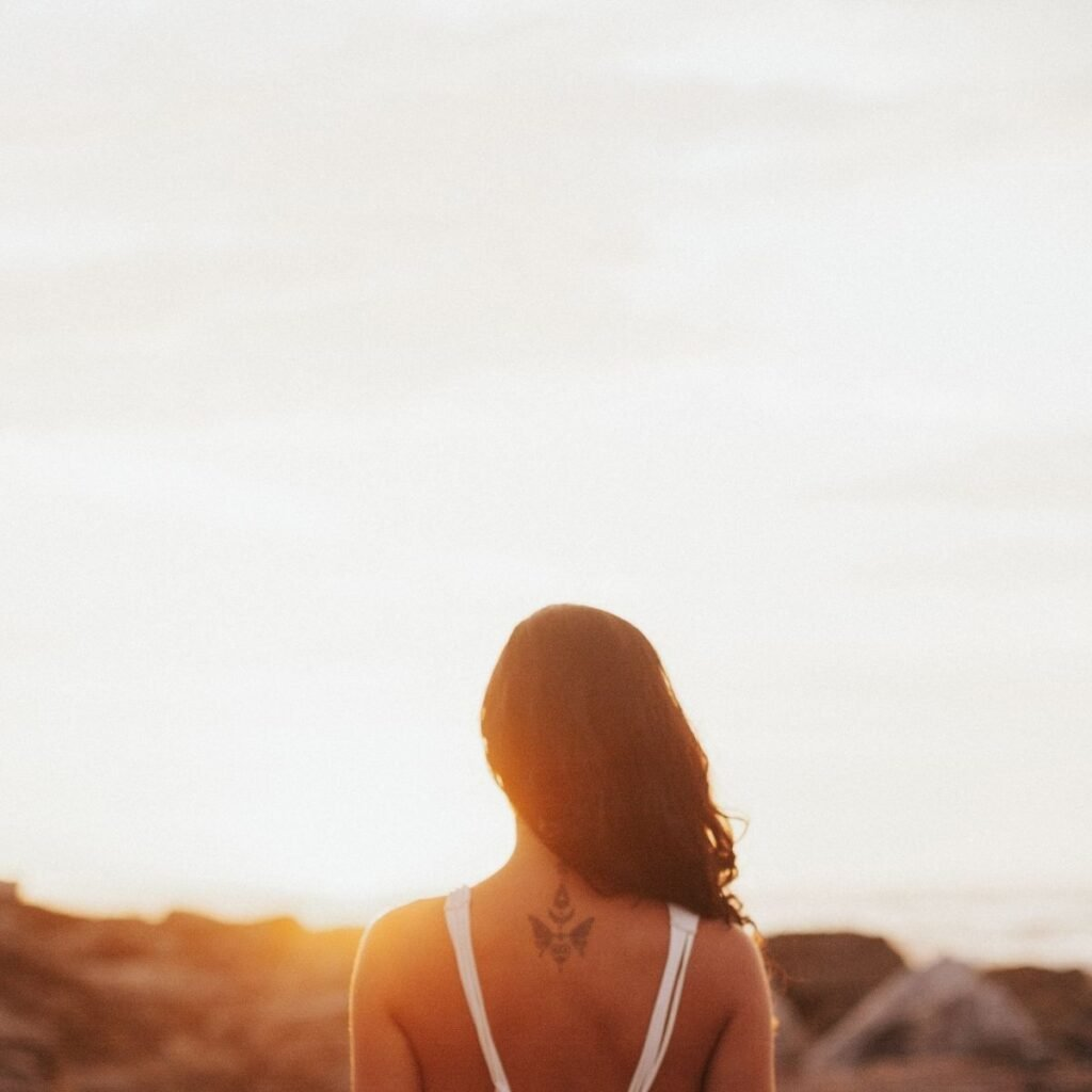 a woman standing in front of a sunset over hills