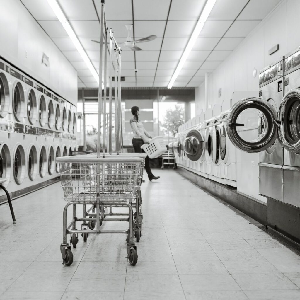 a row of washers and dryers in a laundromat