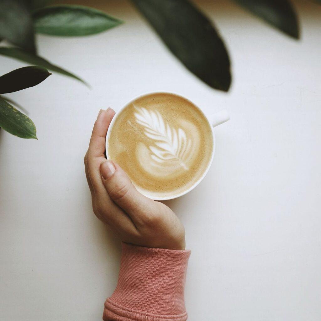 a hand wrapped around a coffee mug