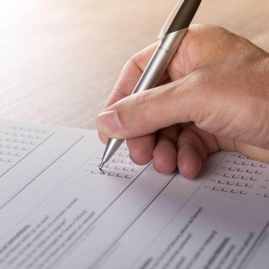 a hand golding a pen filling out a survey