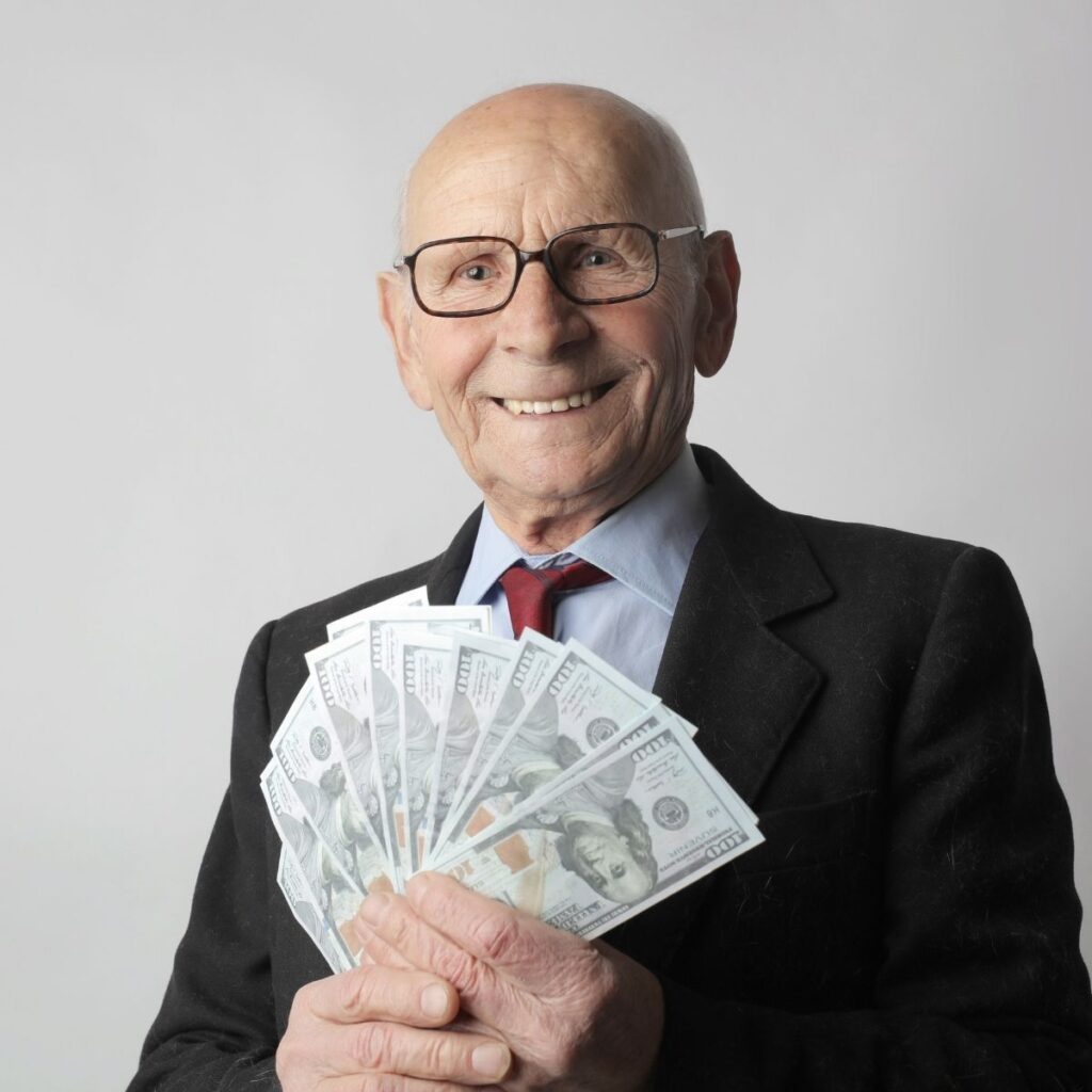 an older man fanning out money and smiling at the camera
