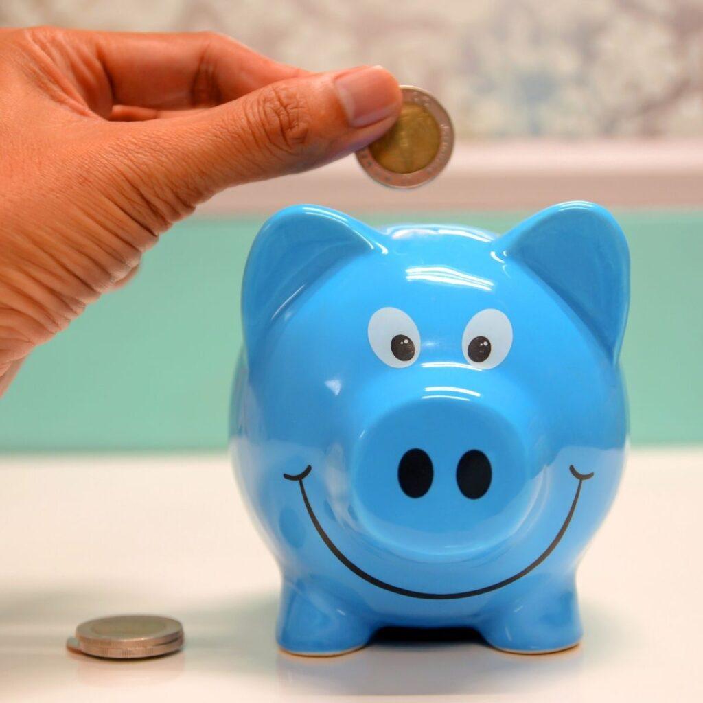 a hand putting a coin into a blue piggy bank