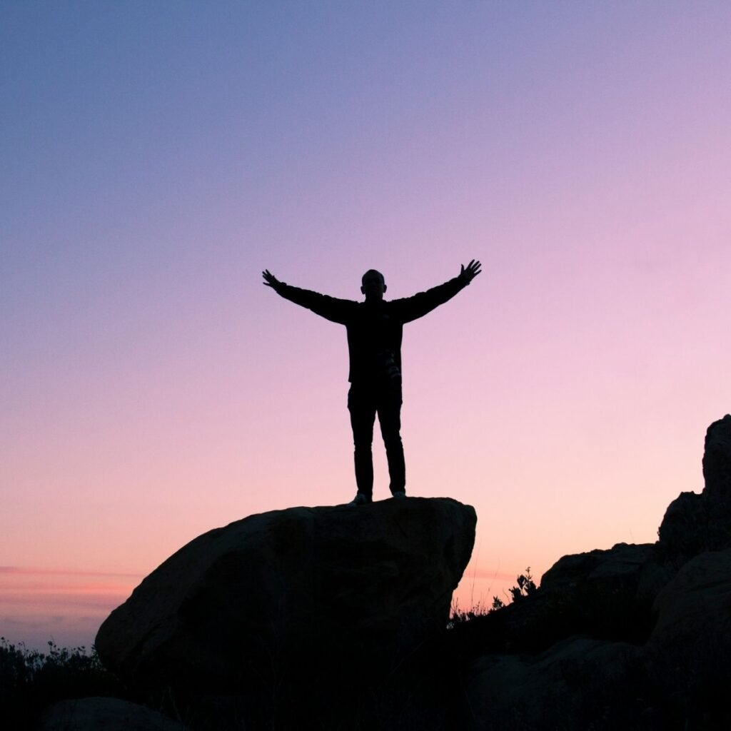 a man standing on a rock looking at the sunset with his arms out