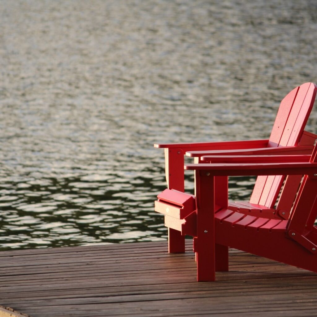2 red deck chairs on a pier over the water
