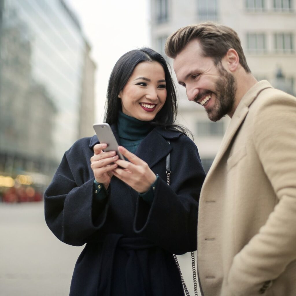 a couple smiling looking at a phone on the street