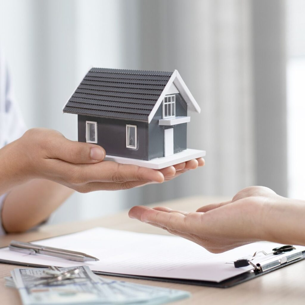 hands holding a grey model house