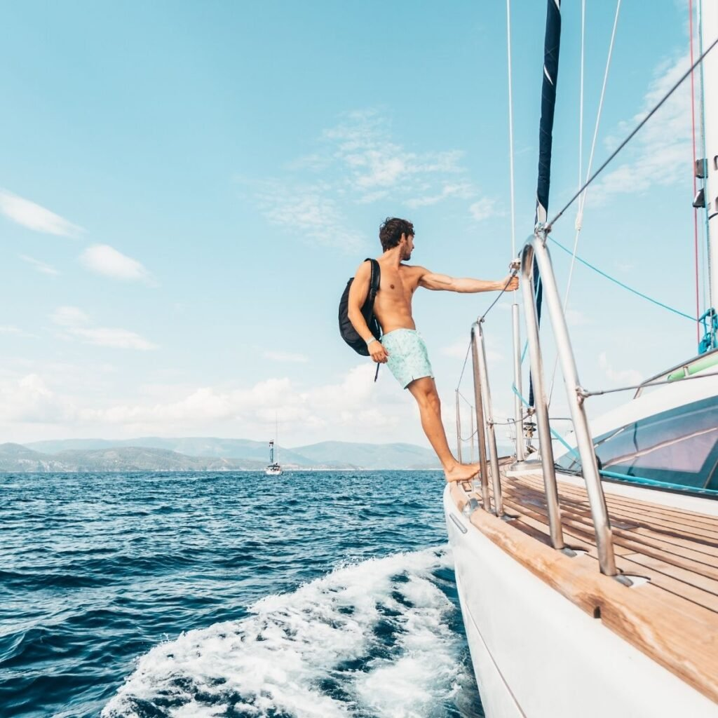 a man hanging off the edge of a yacht