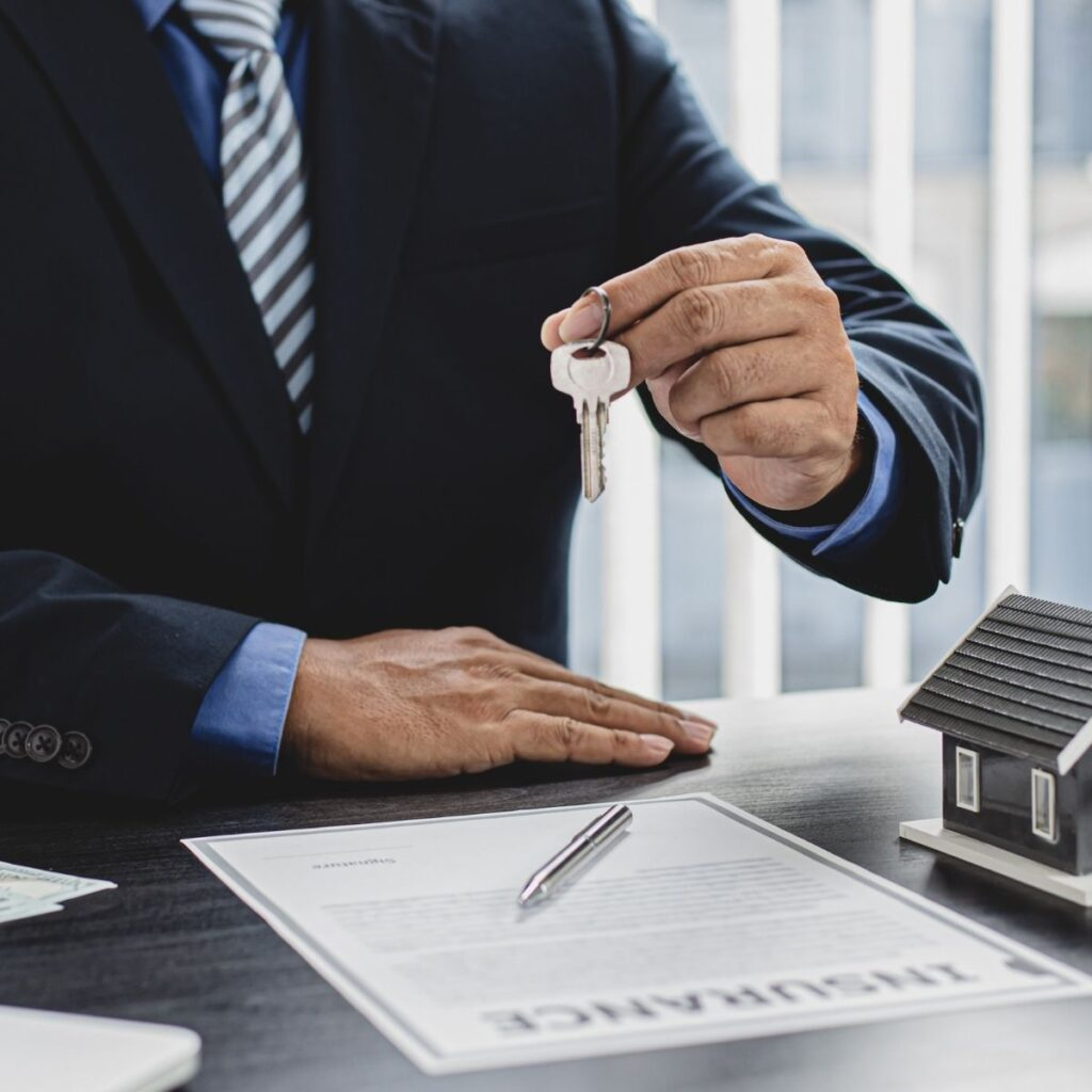 """a man holding a key over a paper that states """"insurance"""""""