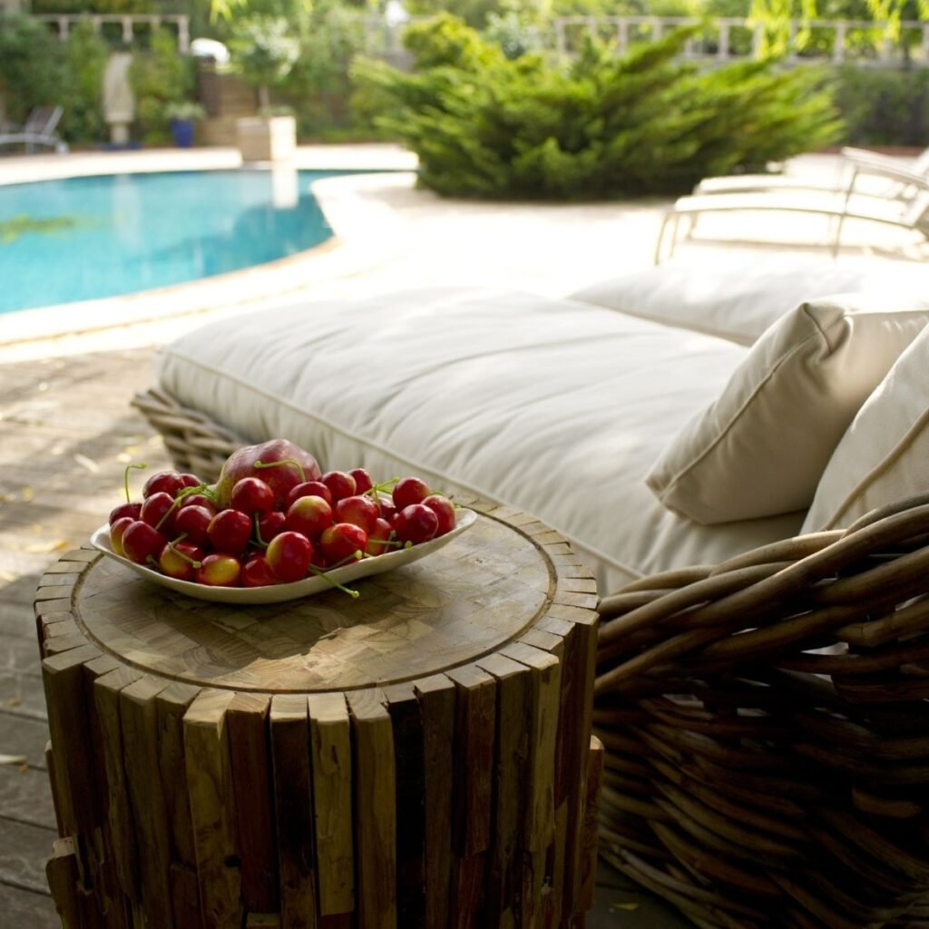 a plate of cherries next to a day bed outside by the pool
