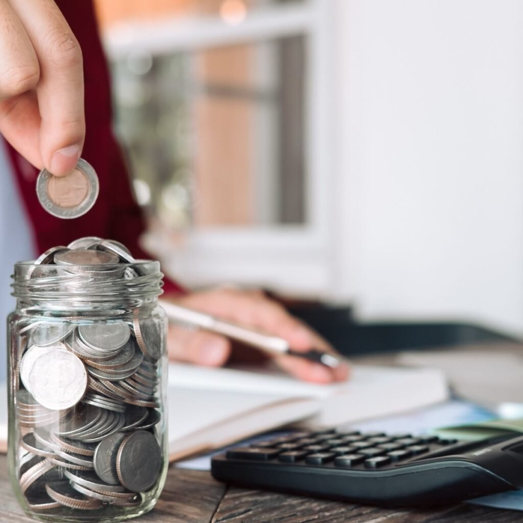 a hand dropping a coin into a jar with a calculator next to it