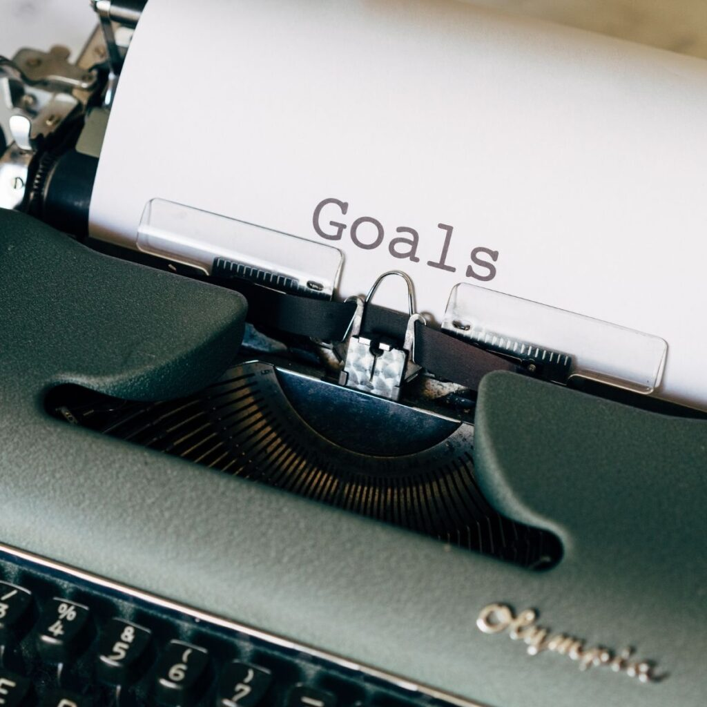 """a typewriter typing """"goals"""" on a piece of paper"""