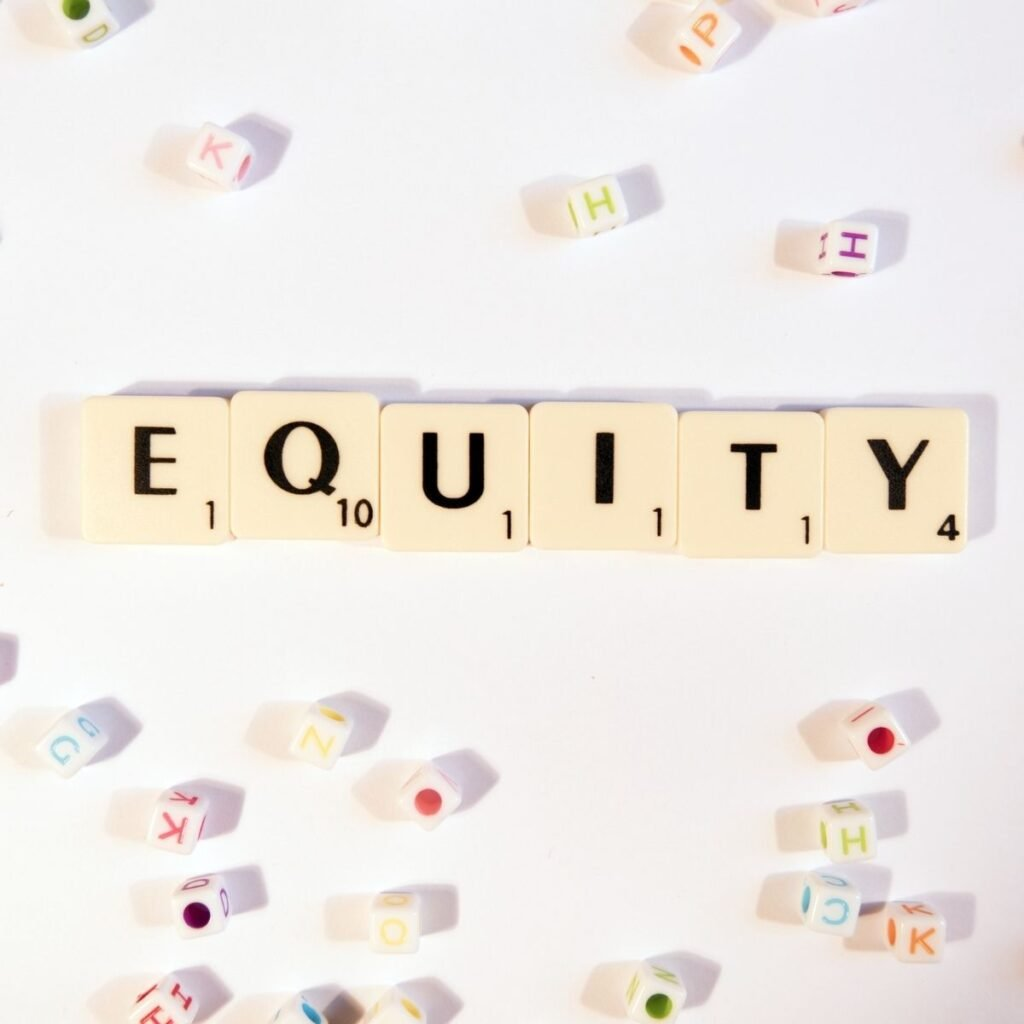 """scrabble pieces spelling out """"equity"""" on a table with other pieces"""