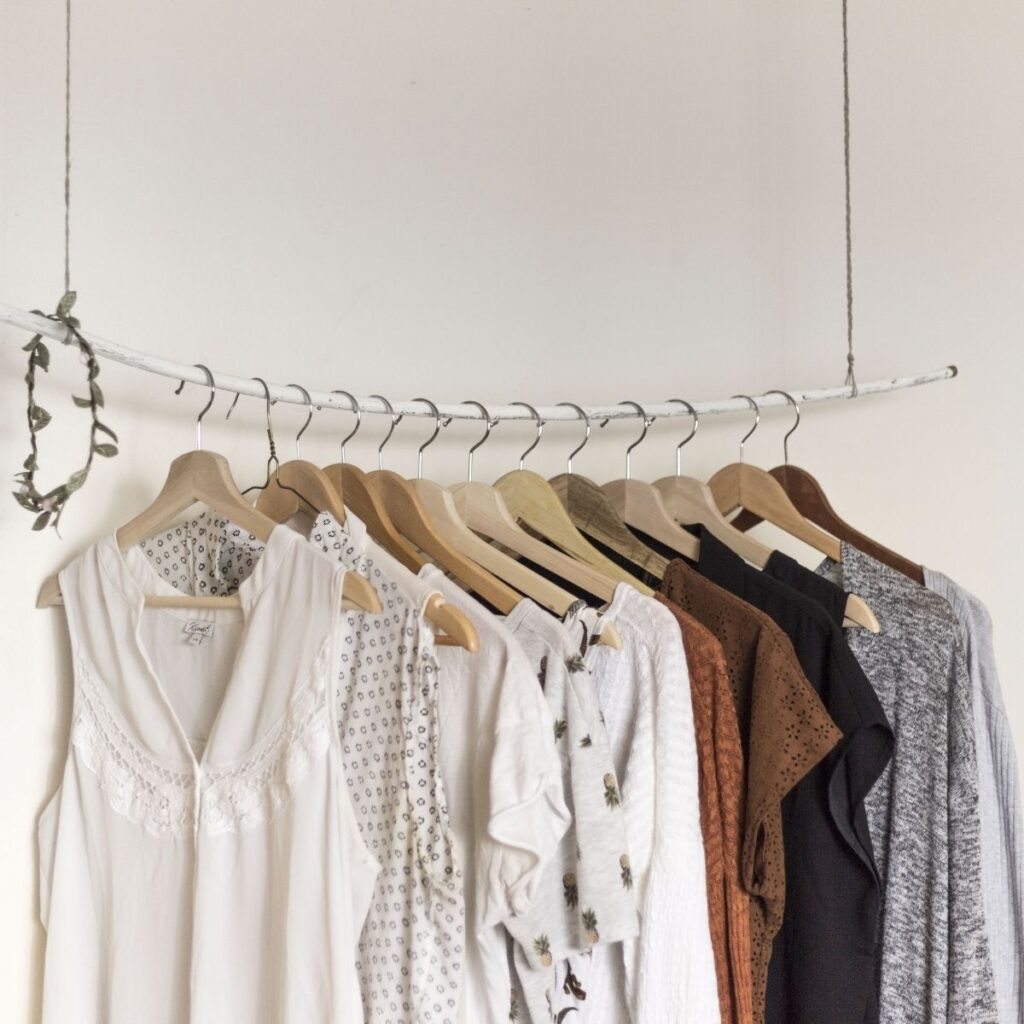 light colored clothes hanging on a rack