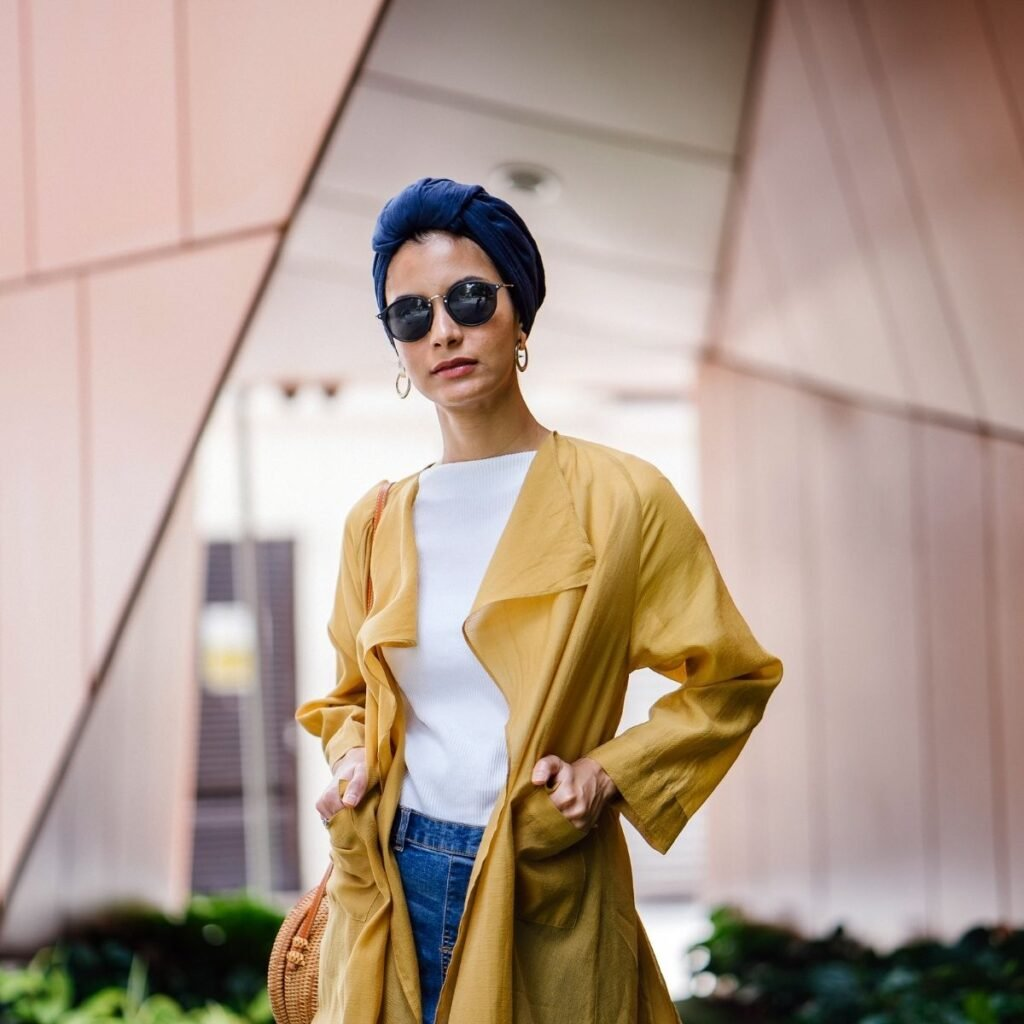 a woman in a yellow jacket and sunglasses looking at the camera