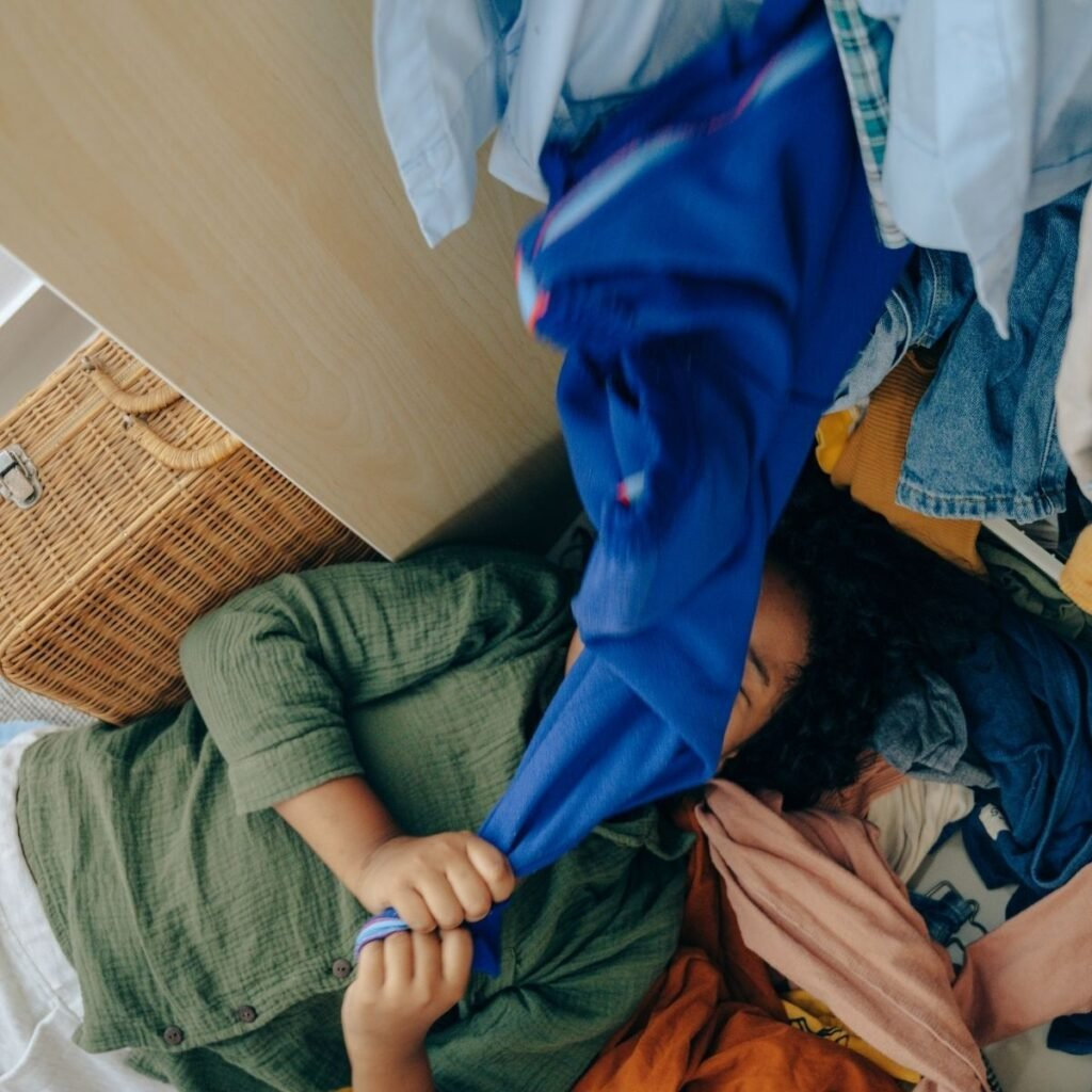 a woman laying on the closet floor pulling clothes over her