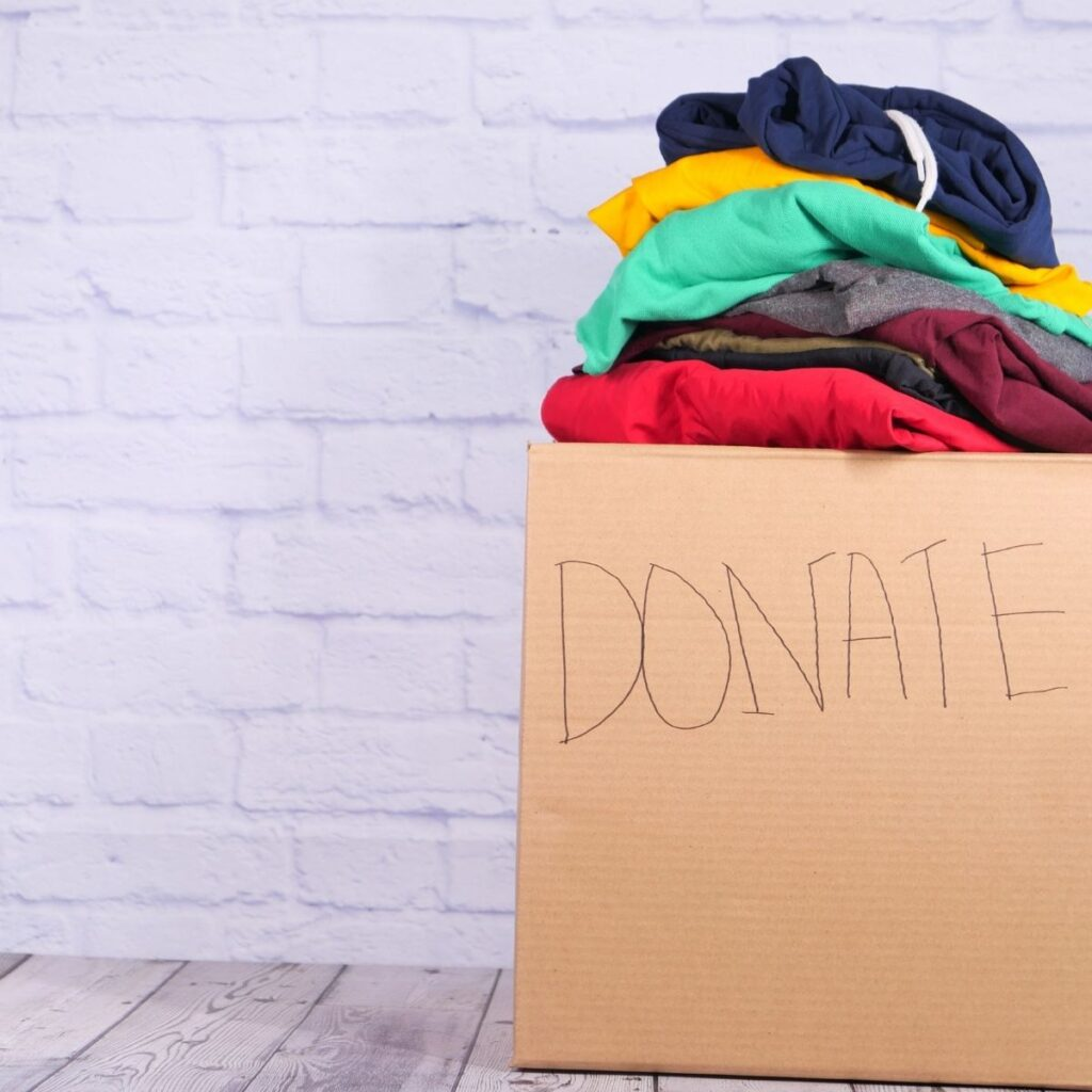 """a box of folded clothes saying """"donate"""""""