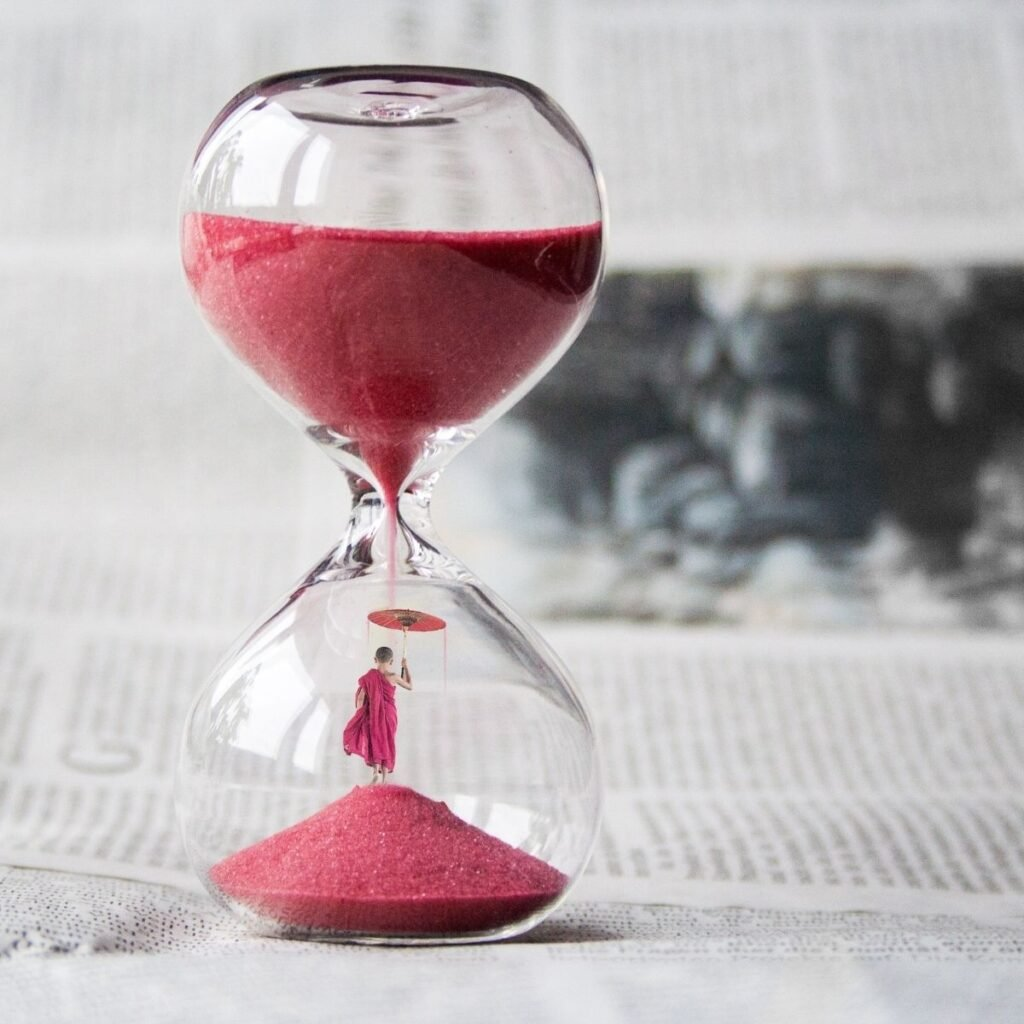 an hourglass on a table filled with red sand