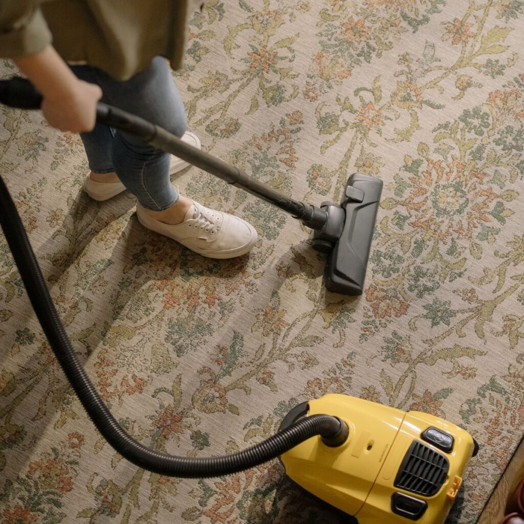a person vacuuming a rug