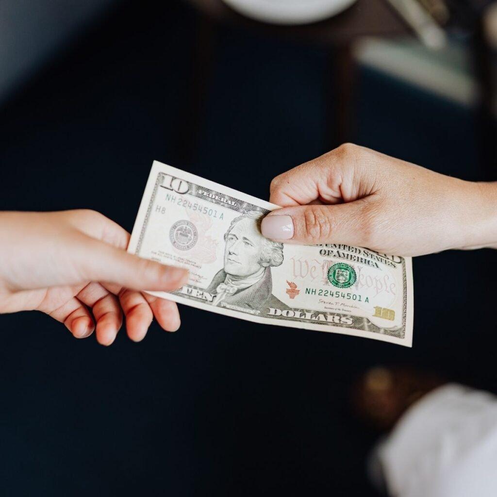 2 hands exchanging a dollar bill