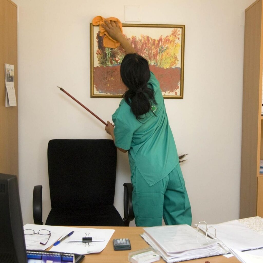 a housekeeper cleaning a picture frame