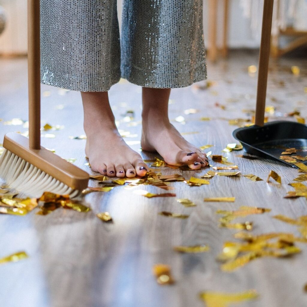 confetti on a floor with a person holding a broom and dustpan